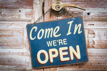 Ven adentro estamos abiertos a la puerta de madera, estilo retro de la vendimia Foto de archivo - 61216667