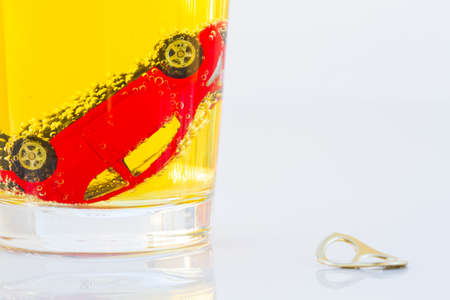 intoxicate: horizontal photo of red toy car in a glass of beer isolated on white background. Drunk-driving Prevention Concept. Stock Photo
