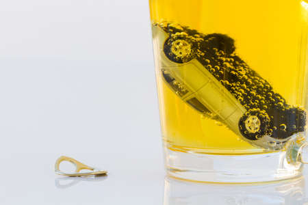 intoxicate: horizontal photo of toy car in a glass of beer isolated on white background. Drunk-driving Prevention Concept.