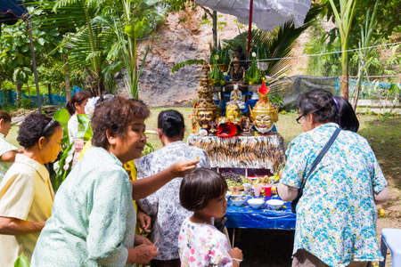CHIANG RAI, THAILAND - SEPTEMBER 1 : unidentified hermit in tiger-skin cloth and a woman ritualising in front of altar table on September 1, 2016 in Chiang rai, Thailand.
