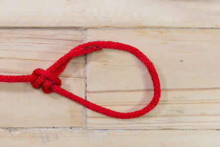 tightening: bowline knot made from red synthetic rope, tightening on wooden background.