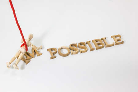 personal perspective: Changing the word impossible to possible with wooden dummy hanging on the red rope