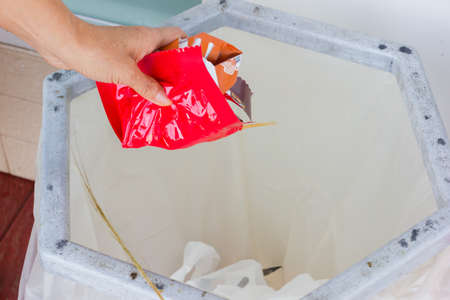 closeup hand throws away red waste material into trash container. Stock Photo