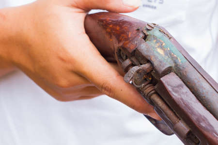 horizontal photo of closeup hand holding old gun, selective focus on the gun. Stock Photo