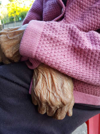 closeup hand of old asian woman with violet pullover