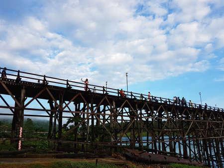 KANCHANABURI, THAILAND - NOVEMBER 25: unidentified tourist enjoying and walking on the old wooden Mon Bridge in Sangkhla Buri on November 25, 2016 in Kanchanaburi, Thailand