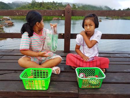thanaka: KANCHANABURI, THAILAND - NOVEMBER 25: unidentified Burmese girls preparing thanaka powder for traveler at the old wooden Mon Bridge in Sangkhla Buri on November 25, 2016 in Kanchanaburi, Thailand Editorial