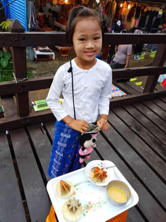 KANCHANABURI, THAILAND - NOVEMBER 25: unidentified Burmese girl preparing thanaka powder for traveler at the old wooden Mon Bridge in Sangkhla Buri on November 25, 2016 in Kanchanaburi, Thailand