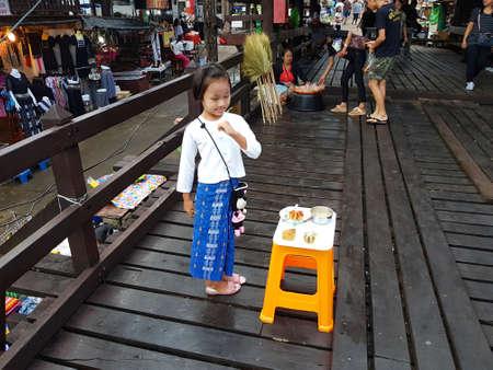 thanaka: KANCHANABURI, THAILAND - NOVEMBER 25: unidentified Burmese girl preparing thanaka powder for traveler at the old wooden Mon Bridge in Sangkhla Buri on November 25, 2016 in Kanchanaburi, Thailand