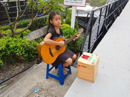 census: KANCHANABURI, THAILAND - NOVEMBER 26: unidentified asian girl playing guitar for donating on Bridge on the river Kwai on November 26, 2016 in Kanchanaburi, Thailand Editorial