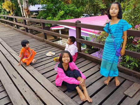 KANCHANABURI, THAILAND - NOVEMBER 25: unidentified Burmese girls preparing thanaka powder for traveler at the old wooden Mon Bridge in Sangkhla Buri on November 25, 2016 in Kanchanaburi, Thailand Editorial