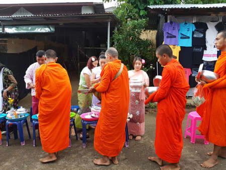 KANCHANABURI, THAILAND - NOVEMBER 25: unidentified people, give food offerings to monks in the morning at Sangkhlaburi on November 25, 2016 in Kanchanaburi, Thailand