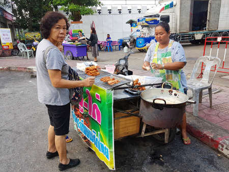 most creative: KANCHANABURI, THAILAND - NOVEMBER 26: unidentified fat woman selling fried chicken to a customer  on November 26, 2016 in Kanchanaburi, Thailand Editorial