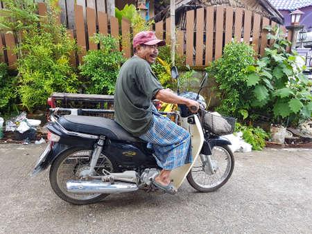 KANCHANABURI, THAILAND - NOVEMBER 25: unidentified Burmese man riding tricycle in Sangkhla Buri on November 25, 2016 in Kanchanaburi, Thailand