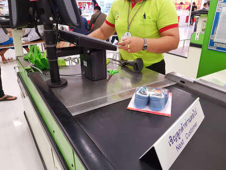CHIANG RAI, THAILAND - FEBRUARY 15 : female seller cashier using barcode scanner in supermarket on February 15, 2017 in Chiang rai, Thailand.