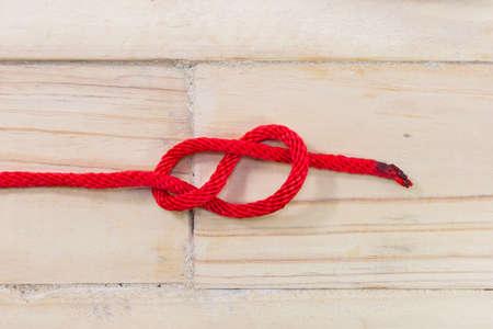 Nudo de ocho hecha con cuerda de color rojo sobre fondo de madera. Foto de archivo - 73119136