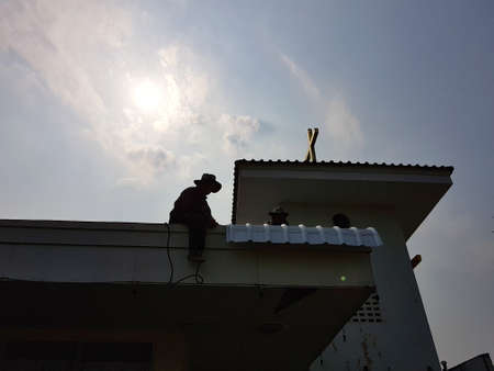CHIANG RAI, THAILAND - MARCH 29 : silhouette unidentified workers repairing or changing roof of Thai protestant church on March 29, 2017 in Chiang rai, Thailand.