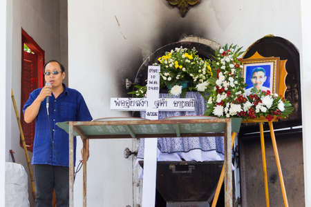 undertaker: CHIANG RAI, THAILAND - APRIL 19 : unidentified asian man speaking next to the white cross and a coffin on April 19, 2017 in Chiang rai, Thailand. Editorial