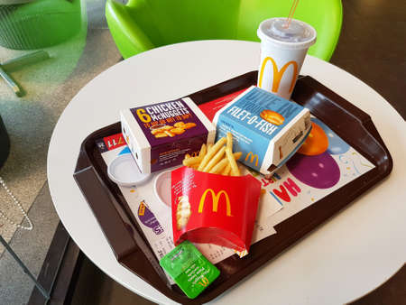 CHIANG RAI, THAILAND - MARCH 1 : fish burgers, french fries, soft drink and nuggets on table at McDonald's restaurant on March 1, 2017 in Chiang rai, Thailand