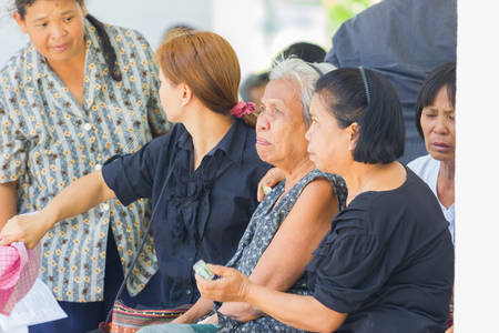 undertaker: CHIANG RAI, THAILAND - APRIL 19 : unidentified asian old woman crying in thai traditional Christian funeral on April 19, 2017 in Chiang rai, Thailand.