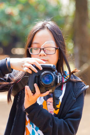CHIANG RAI, THAILAND - FEBRUARY 12 : Unidentified little asian girl with glasses and eye bandage using DSLR camera on February 12, 2017 in Chiang rai, Thailand. Editorial