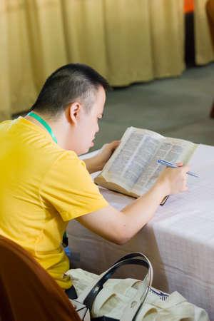 PHETCHABURI, THAILAND - APRIL 7 : unidentified down syndrome boy reading bible on the beach on April 7, 2017 in Phetchaburi, Thailand.