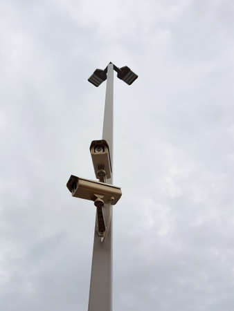 Security CCTV camera in cloudy sky at a gas station in Thailand Stock Photo