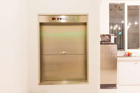 Dumbwaiter lift elevator in a kitchen of rich house used for carrying food or goods Фото со стока