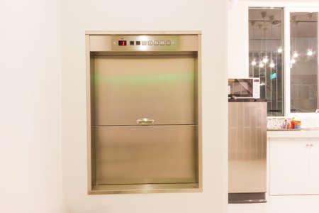 Montacargas ascensor en una cocina de casa rica utilizada para transportar alimentos o bienes Foto de archivo - 79996731