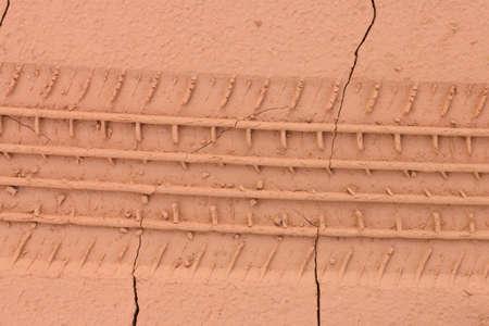 Wheel tracks on the brown soil.