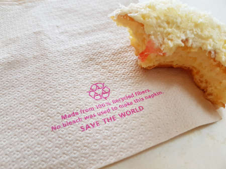 horizontal photo of recycle tissue paper with piece of donut