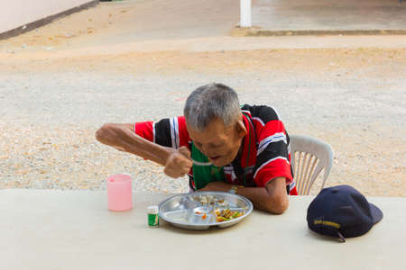 CHIANG RAI, THAILAND - FEBRUARY 19 : unidentified old asian leprosy man with cap eating food on February 19, 2016 in Chiang rai, Thailand.