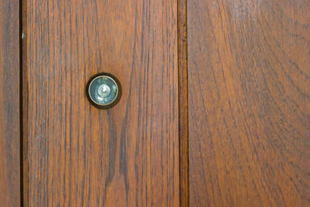 Peephole on the wooden door with copyspace