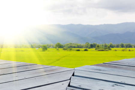 Old vintage planked wood table in perspective on the background of rice field landscape with lens flare, can be used for display or montage your products. Mock up for displaying product. Stock Photo