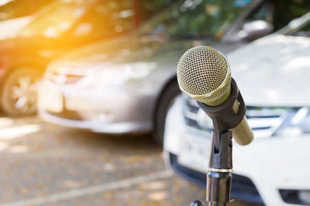 microphone on a stand with blurred vehicles in car park background, Copyspace on the left. Stock Photo