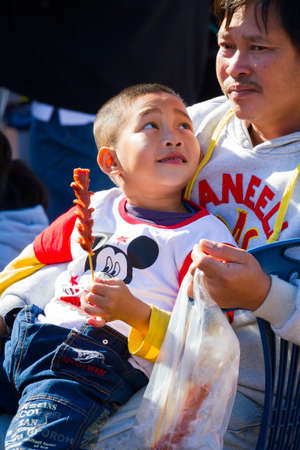 CHIANG RAI, THAILAND - JANUARY 8 : Unidentified asian boy with sausage on his hand looking at his father on January 8, 2016 in Chiang rai, Thailand. Editorial