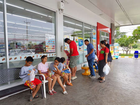 comercial: CHIANG RAI, THAILAND - MAY 7 : unidentified asian people or tourists sitting and standing in front of 7-eleven shop on May 7, 2017 in Chiang rai, Thailand.