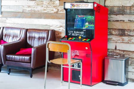 BANGKOK, THAILAND - OCTOBER 19: retro red game coin console or Vintage arcade machine at wooden wall background on October 19, 2017 in Bangkok, Thailand.