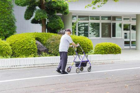 TOKYO, JAPAN - SEPTEMBER 16 : unidentified asian old leprosy man walking with wheel waker  for exercising in Tama Zensho Hospital on September 16, 2017 in Tokyo, Japan.