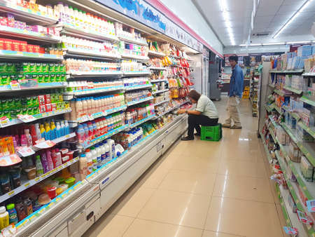 CHIANG RAI, THAILAND - NOVEMBER 6 : unidentified convenience store staff checking dairy products on the shelf  on November 6, 2017 in Chiang rai, Thailand.