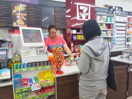 CHIANG RAI, THAILAND - NOVEMBER 6: Niet geïdentificeerd Aziatisch vrouwenwachten om bij de kassierteller bij een gemakswinkel 7-Elf op 6 November, 2017 in Chiang Rai, Thailand te betalen.