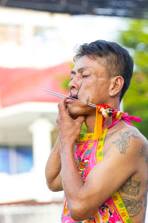 PHUKET, THAILAND - OCT 12, 2018: Chinese thai monk possessed by his god walking with his mouth pierced with hair pins in Vegetarian Festival at Phuket Town on October 12, 2018 in Chiang rai, Thailand. Фото со стока - 134631494