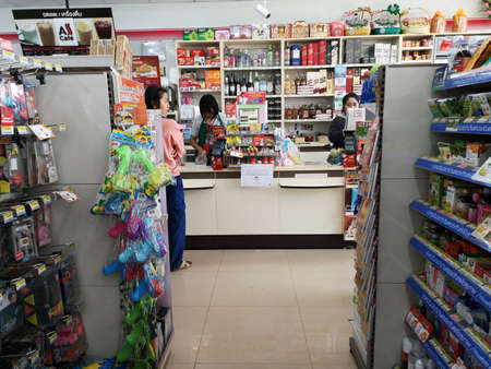 CHIANG RAI, THAILAND - JANUARY 10 : unidentified woman paying money at cashier in 7-eleven store on January 10, 2019 in Chiang rai, Thailand.