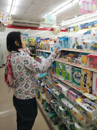 CHIANG RAI, THAILAND - JANUARY 10 : unidentified woman choosing goods in 7-eleven store on January 10, 2019 in Chiang rai, Thailand.