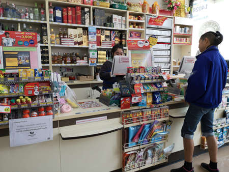 CHIANG RAI, THAILAND - JANUARY 10 : unidentified man paying money at cashier in 7-eleven store on January 10, 2019 in Chiang rai, Thailand.