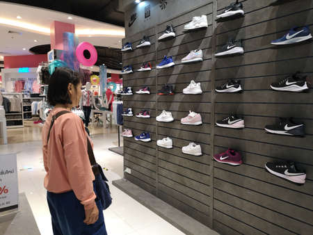 CHIANG RAI, THAILAND - MARCH 7, 2019 : unidentified woman choosing Nike shoes on display in department store on March 7, 2019 in Chiang rai, Thailand. Editorial