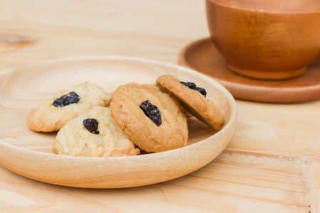 Fresh baked butter cookies with raisins on wooden background