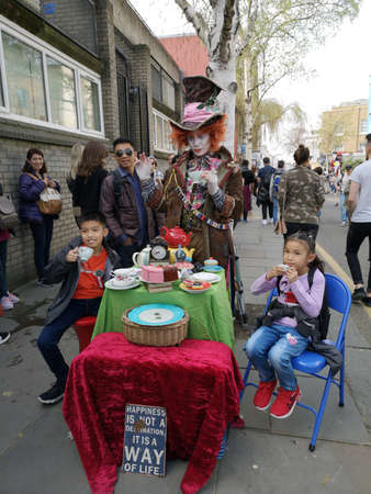 LONDON, UNITED KINGDOM - MARCH 30, 2019 : unidentified asian children sitting with street performer at Portobello Market in Notting Hill on March 30, 2019 in London, United Kingdom.