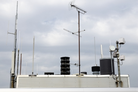 Urban view of multitude of antennas on the roof photo