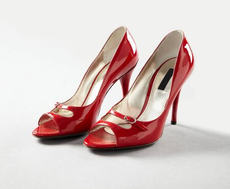 stilleto: A pair of red female shoes on a white background